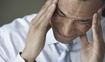 middle aged office worker with visible tension headache