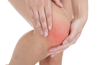 woman holding right knee in pain
