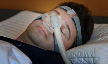 young man hooked up to nasal breathing machine