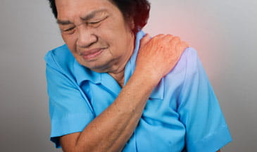 middle aged hispanic woman with shoulder pain